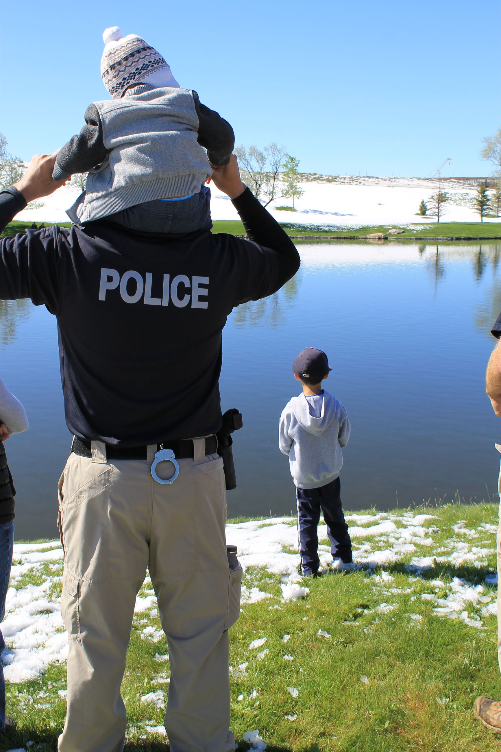 Small child on Police Oficer shoulder looking at pond