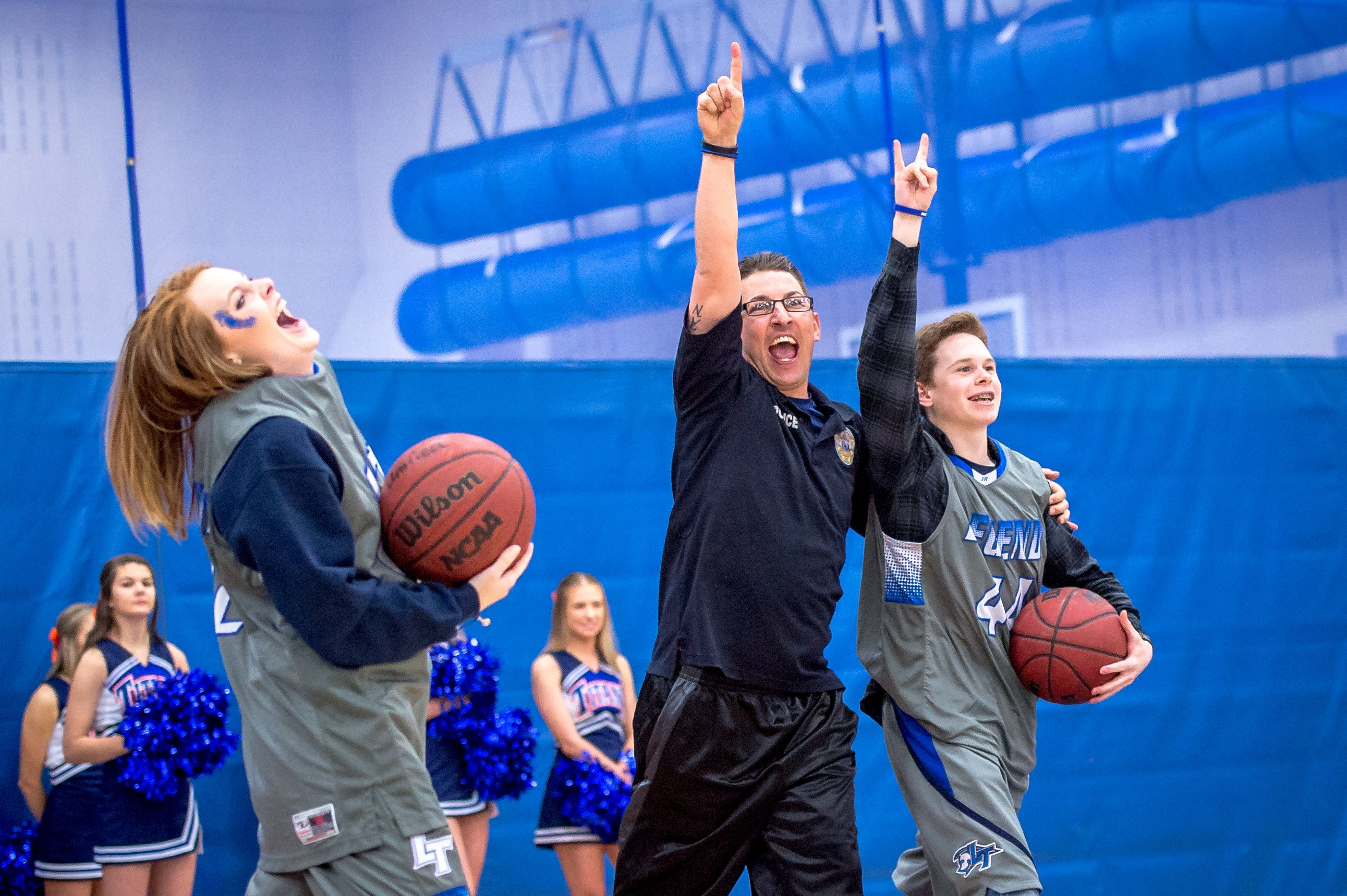 Officer with Legend Unified Basketball players on the court
