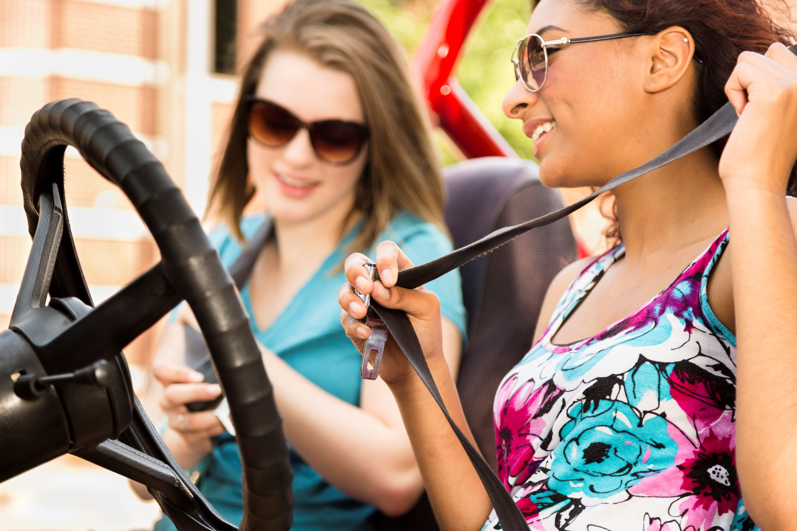 Teens putting on seat belts in a jeep