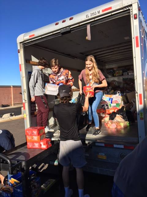 people unloading food from a box truck